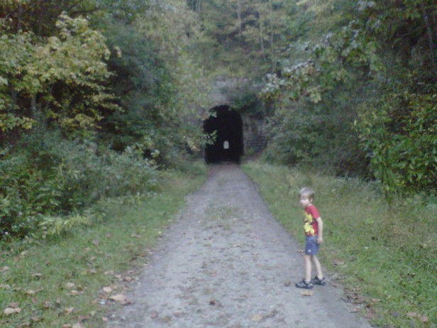 My oldest son stands outside an old train tunnel that is now rail-trail