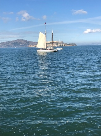 The Alma, part of the National Park Service, allows you to learn how to hoist the sails in the bay. Alcatraz is in the background.