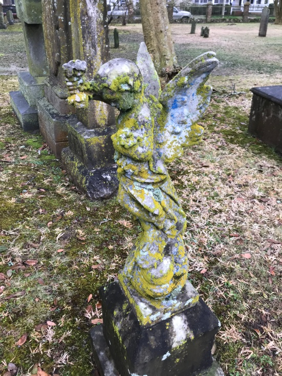 A young angel is covered with fungus and moss.