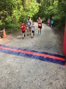 Mountain Papa (gray shirt), Mountain Kid 2 (red) and another runner help Mountain Kid 3 cross the finish line of the 5K.