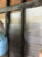 A visitor looks at a recent attempt to recreate white wash in a building on the Iredell property. The boards are different colors because of how the wood absorbed the white wash.