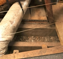 The attic of the 1767 courthouse is filled with hand-hewn beams. In the floor, you can see pegs sticking out of the floor. They hold up the wooden panelling that lines the walls of the second-floor room.
