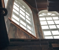 The windows of the two-tierred cupola shine light on the courthouse bell. The wood between the windows are lined with graffiti.