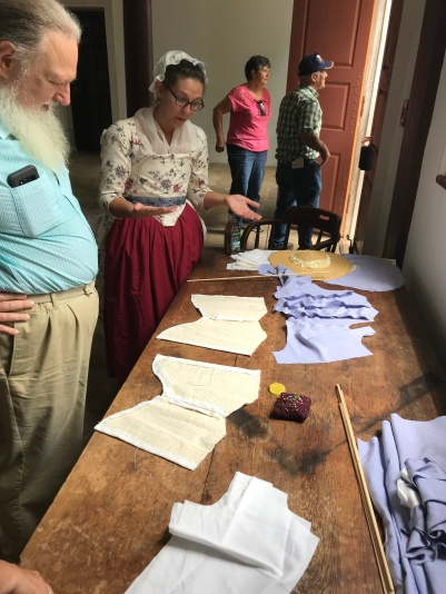 Re-enactor and costume designer Kayla Collins talks about a dress and undergarments she is working on . The costume she is wearing is based on an Italian pattern from the late 1700s, but her arm movements are limited. The dress she's working on will allow her more movement.