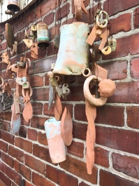 A handmade clay windchime on the side of the Pocosin Art exhibit building.