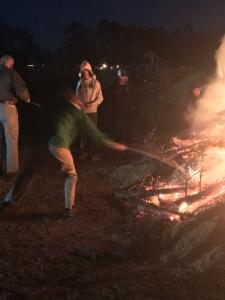 A teenage roasts a marshmallow in a bonfire.